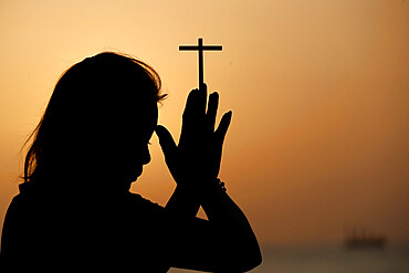 Silhouette of faithful woman praying with Christian cross at sunset as concept for religion, faith, prayer and spirituality, Dubai, United Arab Emirates, Middle East