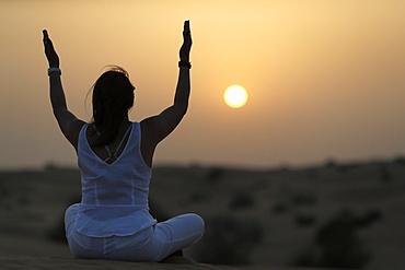 Sunset meditation in the desert at sunset, as concept for religion, faith, prayer and spirituality, Dubai, United Arab Emirates, Middle East
