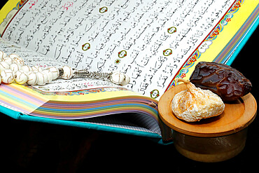 Holy Quran book with prayer beads and dates. Faith and religion. Ramadan concept.