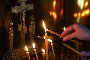 Faithful lighting a candle in Saint Teaodor Tiron (Ciuflea) Cathedral and Monastery, Chisinau, Moldova, Europe