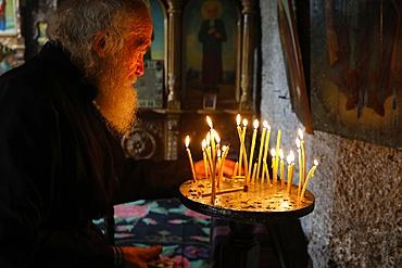 Monk tidying candles in Orhei Vecchi Monastery, Orhei, Moldova, Europe