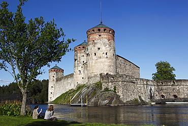 Girls relaxing beside Olavinlinna Medieval Castle (St. Olaf's Castle), Savonlinna, Saimaa Lake District, Savonia, Finland, Scandinavia, Europe