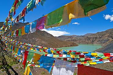 Prayer flags above an artifical lake near the Karo-La Pass, Tibet, China, Asia