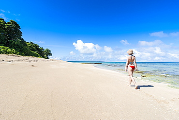 Woman walking on a white sand beach on a little islet in Haapai, Haapai Islands, Tonga, South Pacific, Pacific