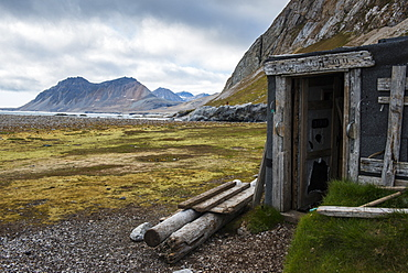 Abandoned hut on Alkhornet with a huge rock in the background, Svalbard, Arctic