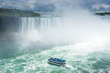 Tourist boat in the mist of the Horseshoe Falls (Canadian Falls), Niagara Falls, Ontario, Canada, North America