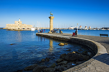 The old Agios Nikolaos fortress and lighthouse in Mandraki Harbour with deer statue in foreground, Rhodes Town, Rhodes, Dodecanese Islands, Greek Islands, Greece, Europe