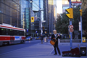 Street musician playing guitar with brown paper bag covering his head, Toronto, Ontario, Canada, North America
