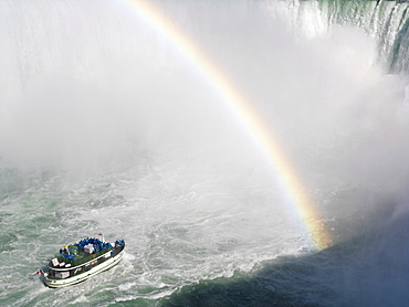 Maid of the Mist tour boat approaching the Canadian Falls with a rainbow, Niagara Falls, Ontario, Canada, North America