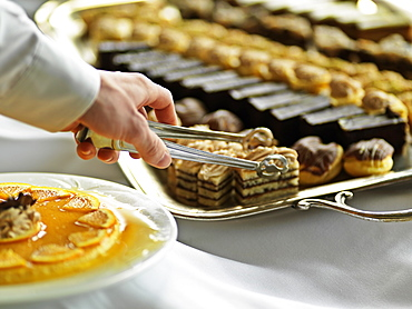 Dessert tray with hand and tongs reaching for pastry, Jasper Park Lodge, Jasper, Alberta, Canada, North America