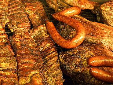 Ribs, and beef brisket grilling in an open pit BBQ grill in Texas BBQ style, Houston, Texas, United States of America, North America