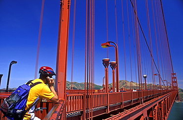 Cyclist using cell phone on the Golden Gate Bridge, San Francisco, California, United States of America, North America