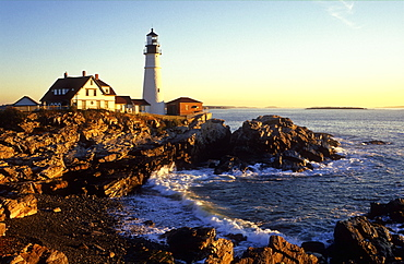 View of Portland Head Lighthouse in the early morning, with waves crashing on rocks in foreground, Cape Elizabeth, Maine, New England, United States of America, North America