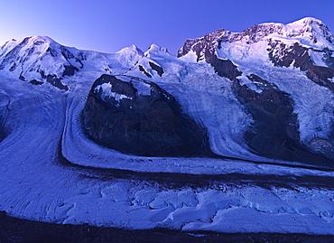 Peaks of Mount Rosa, Liskamm, and Breithorn and the Gorner Glacier as viewed from the Gornergrat under moonlight, Zermatt, Valais, Switzerland, Europe