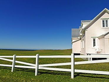 Pink house and with white fence against a blue sky, Riviere-la-Madeleine, Gaspesie, Quebec, Canada, North America