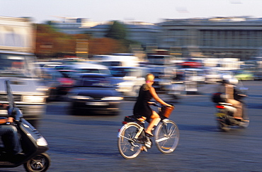 Cyclist in traffic in the Place de la Concorde, and Eiffel Tower behind, Paris, France, Europe
