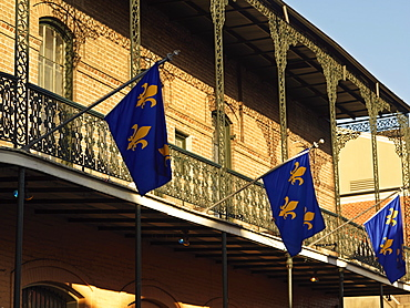 French Quarter building with wrought iron balconies and fleurs de lys flags, New Orleans, Louisiana, United States of America, North America