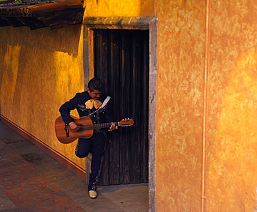 Musician playing guitar in an open doorway, Tequila, Jalisco, Mexico, North America