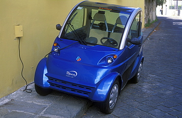 Electric car being charged at wall outlet, Florence, Tuscany, Italy, Europe