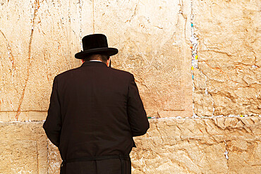 A Jewish man wearing Orthodox clothing prays by the Western Wall (Wailing Wall), Jerusalem, Israel, Middle East - 826-748