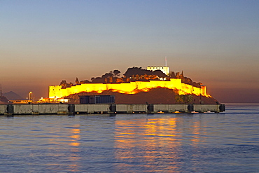 The Byzantine-era fortress, illuminated at dusk, on Guvercin Ada (Pigeon Island), on the Aegean coast, in Kusadasi, Turkey, Asia Minor, Eurasia