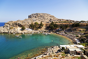 Sun shades line the beach at St. Paul's Bay on a sunny day in Lindos on Rhodes, Dodecanese, Greek Islands, Greece, Europe