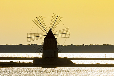 Silhouette of old windmill used to raise water from the Stagnone Lagoon into salt pans south of Trapani, Marsala, Sicily, Italy, Mediterranean, Europe
