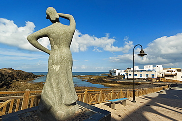 Statue of woman looking out to sea by the old harbour at this north west coast village, El Cotillo, Fuerteventura, Canary Islands, Spain, Atlantic, Europe