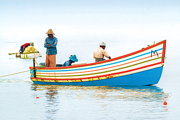 Fishermen in colourful boat on the Arabian Ocean just off popular Marari Beach, Mararikulam, Alappuzha (Alleppey), Kerala, India, Asia