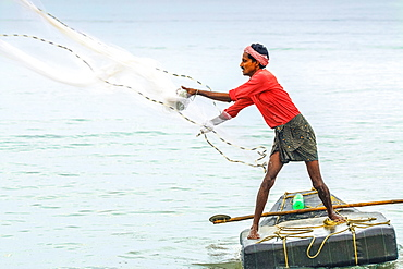 Fisherman casting weighted net on small raft offshore of popular Marari Beach, Mararikulam, Alappuzha (Alleppey), Kerala, India, Asia
