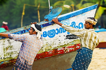 Fishermen pulling heavy old boat on to shore at busy, popular Marari Beach, Mararikulam, Alappuzha (Alleppey), Kerala, India, Asia
