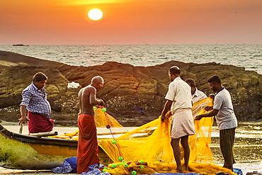 Fishermen cleaning net at sunset on lovely unspoilt Kizhunna Beach, south of Kannur on the north coast, Kannur, Kerala, India, Asia