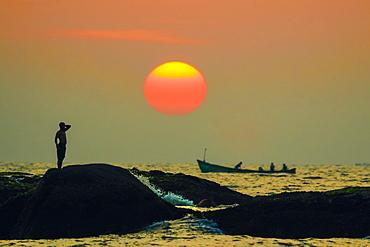 Man on intertidal rocks and fishing boat at sunset on beautiful unspoilt Kizhunna Beach, south of Kannur, Kannur, Kerala, India, Asia