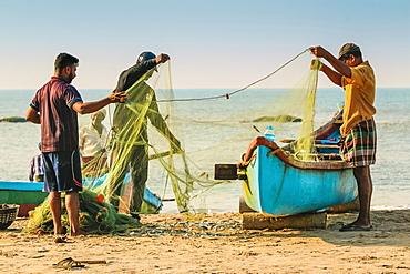 Fishermen cleaning net at beautiful Kizhunna Beach, south of Kannur on the Keralan north coast, Kizhunna, Kannur, Kerala, India, Asia - 83-13226
