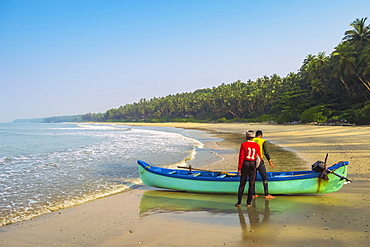 Fishermen with boat on beautiful Kizhunna Beach, south of Kannur on the Keralan north coast, Kizhunna, Kannur, Kerala, India, Asia
