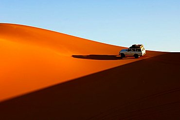 Jeep riding on sa and dune in the Sahara desert escaping the evening shadow Erg Ubari Idhan Awbari Libya