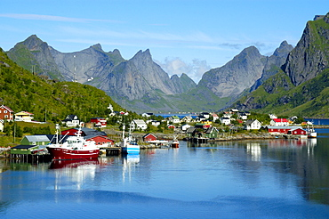 Mountains ships and houses reflect in the fjord Reine Moskenesoya Lofoten Norway