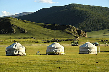 Three yurts ger in the steppe in front of a forested mountain range Orkhon waterfall Mongolia