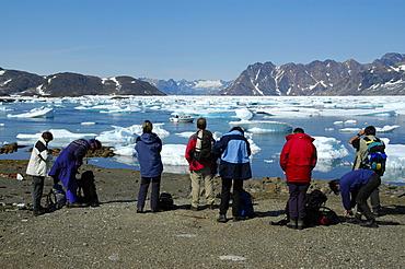 People watch ice pack and icebergs in Ammassalik Fjord near Kulusuk Eastgreenland