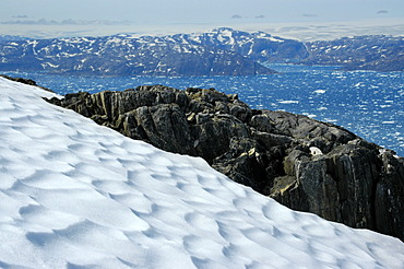 Wide open view over a snow field and rocks to icebergs in Sermilik Fjord Eastgreenland