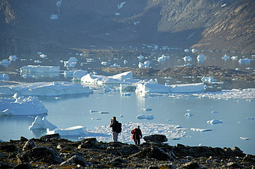 People in front of fjord with icebergs and mountains Nagtivit Kangertivat Fjord Eastgreenland
