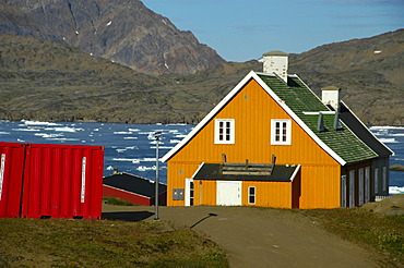 Colourful house at a fjord in settlement Ammassalik Eastgreenland