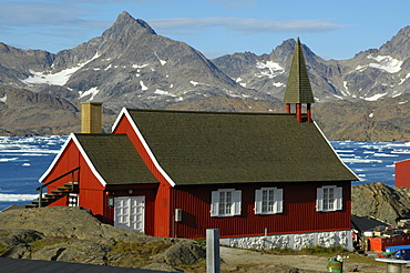 Red church at fjord and mountain chain Ammassalik Eastgreenland