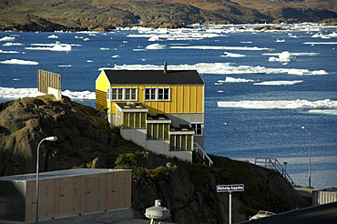 Yellow house above fjord with ice-pack Ammassalik Eastgreenland