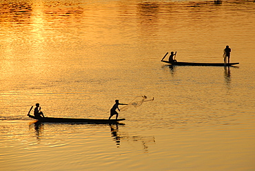Sunset fishermen in boats throwing nets on the Mekong River Muang Khong Si Phan Don Laos