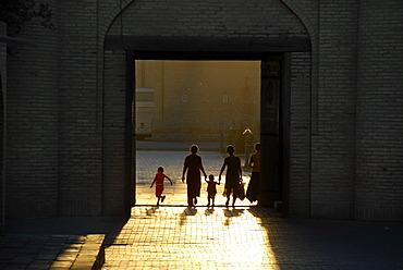 Human silhouettes against sunlight in the Ota Darvoza Gate in the old town Khiva Uzbekistan