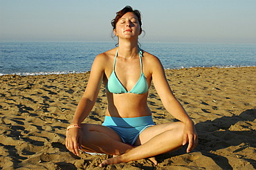 Woman does yoga at the beach