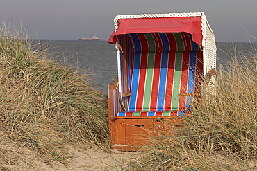 DEU, Federal Republic of Germany, Wangerland, Hooksiel, dunes with empty beach chair North Sea, Jadebusen