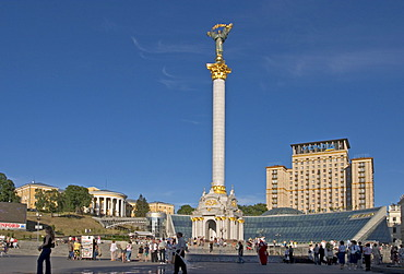 Ukraine Kiev Place of Independence with column of independence and hotel Kiev middle side glasfront of shopping center Globus II Zovtnevyj-palace left side people in front of column of Independence sitting shopping talking blue sky 2004