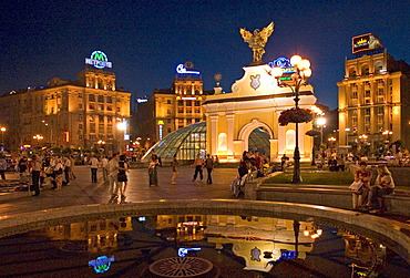 Ukraine Kiev Place of Independence people tourists visitors sit on the place with view to the Pecers´kyi gate with archangel Michael and fountain with water iluminated place with historical buildings of sowjetic realismn architectur national holiday 2004